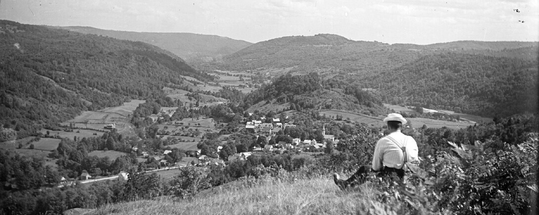Man sitting on hill overlooking Townsend, Vermont