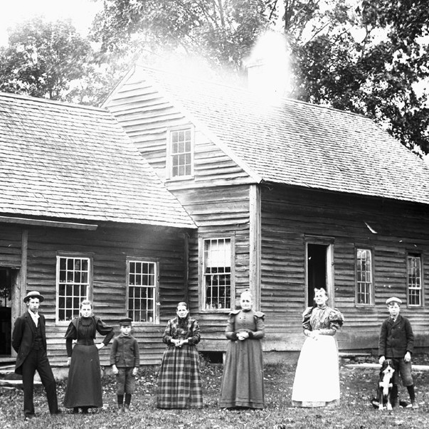 adults and children standing in front of house