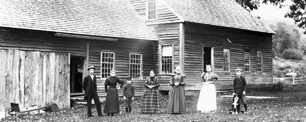 group of adults and children standing in front of a house