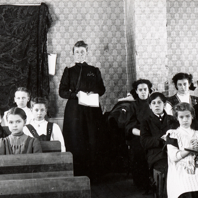 classroom with teacher standing and students sitting at desks