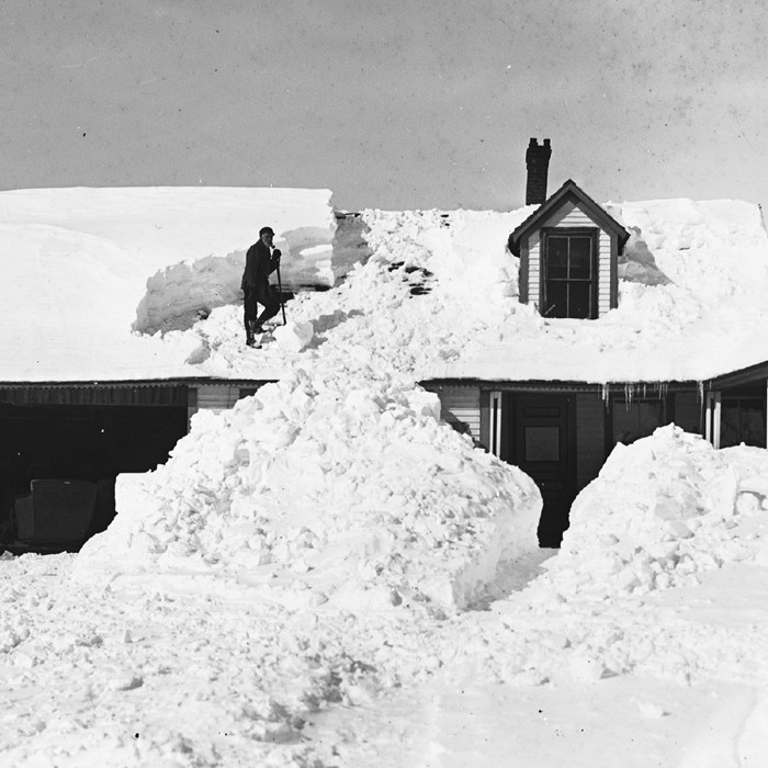Photograph of man shoveling snow from roof.