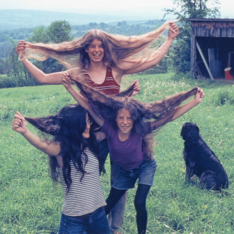 Three girls holding out their long hair
