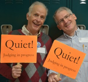 Two men holding signs that say Quiet, Judging in Progress.