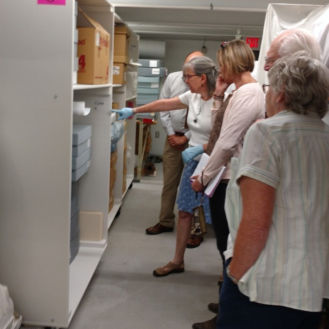person showing museum storage to group of people