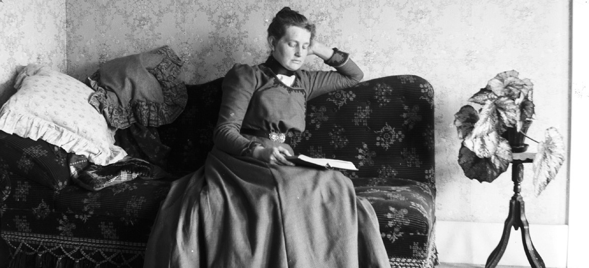 old photo of woman reading book on couch